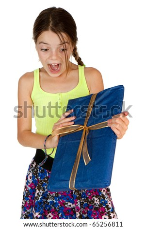 A primary aged girl screams with excitement whilst holding a ribbon wrapped gift. - stock photo
