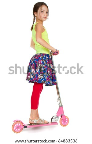 A primary aged girl standing on a pink toy scooter.