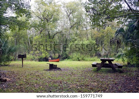 A primitive campsite in a remote tropical forest, with a canoe resting on the creek bank. - stock photo