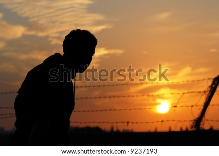 A prisoner yearning for freedom at sunset - stock photo