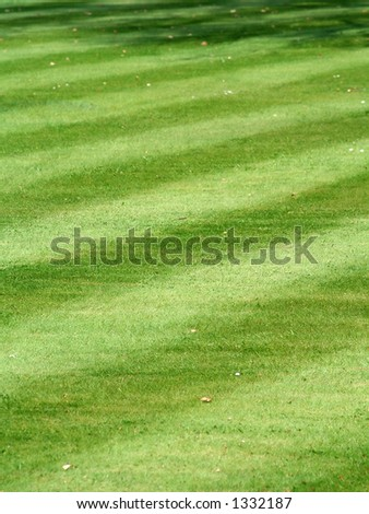 A pristine and accurately-mowed striped grass lawn - stock photo