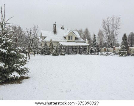 a private house and its garden under snow - stock photo