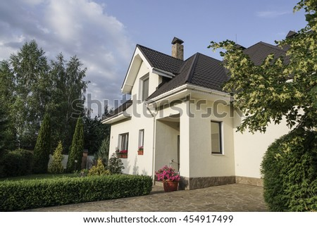 A private house with a garden in a rural area under beautiful sky