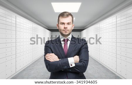 A private manger of a bank with crossed hands is standing in a room with safe deposit boxes. A concept of storing of important documents or valuables in a safe and secure environment. - stock photo