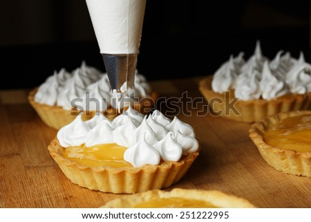 A process of decorating lemon tartlets with meringue icing - stock photo