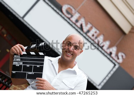A production assistant or movie director holding a clap board or slate in front of the cinemas. - stock photo