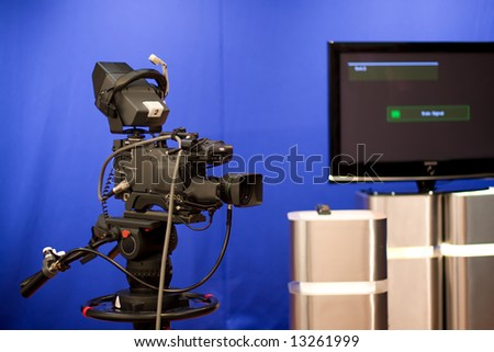 A professional broadcasting television camera in front of a blue screen and set decoration in a studio.