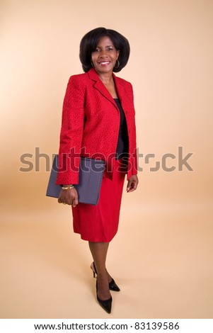 a professional businesswoman in a red suit carrying a laptop. - stock photo