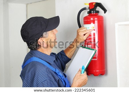A Professional checking aFire extinguisher - stock photo