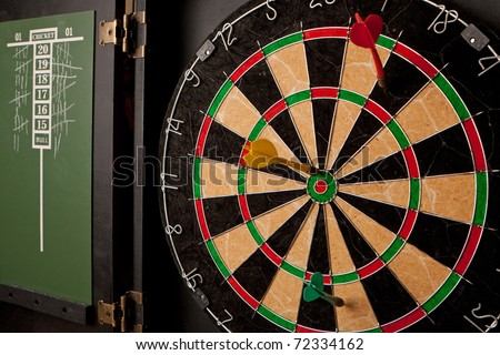 A professional dart board enclosed in a cabinet with slate chalkboard score boards. - stock photo