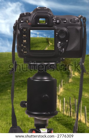 A professional digital camera DSLR on a tripod - stock photo
