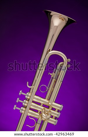 A professional gold trumpet isolated against a spotlight purple background.