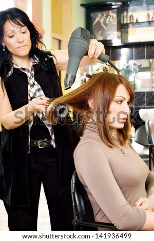 A professional hairdresser dries brunette hair with a hair dryer in salon