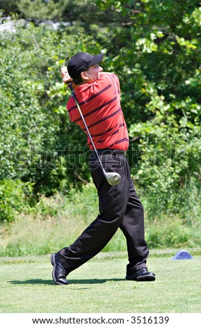 A professional looking male golfer completes a long drive from the tee box. - stock photo