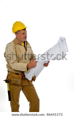 A professional male construction contractor worker wearing a hard hat and tool belt is holding construction blue print plans.