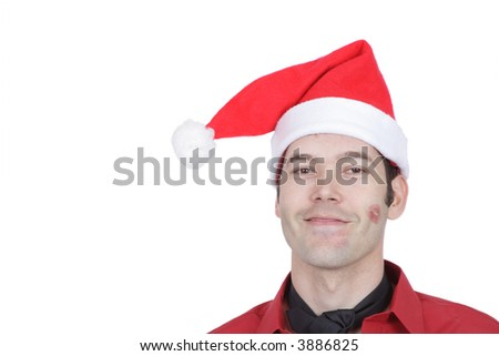 A professional man at an office Christmas Party wears a silly grin with his tie mis-tied and red lipstick kisses on his face.
