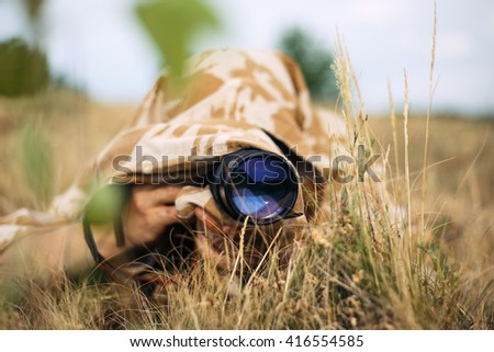 A professional nature/wildlife photographer at work. He covered by shirt from the camouflage fabrics. Shirt make his invisible in the grass. The camera lens has blue color of front lens, like the eye. - stock photo