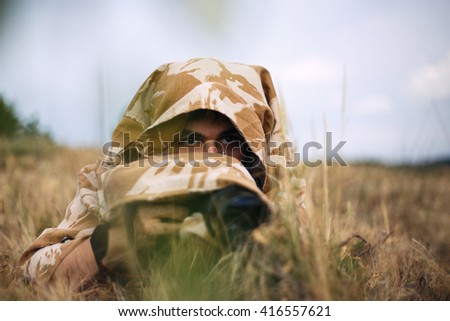 A professional nature/wildlife photographer at work. He covered by shirt from the camouflage fabrics. Camouflage shirt make his invisible in the grass. Man is shooting foxes at meadow. - stock photo