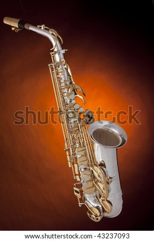 A professional silver and gold alto saxophone isolated against a spotlight dark yellow background.