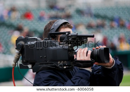 A professional videographer at a baseball game. - stock photo