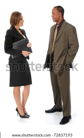 A professionally dressed man and woman standing against a white background while talking to each other - stock photo