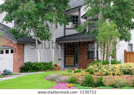 A professionally landscaped yard beautifies a corner front entrance. - stock photo