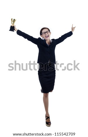 A proud businesswoman celebrating her winning by holding her trophy - stock photo