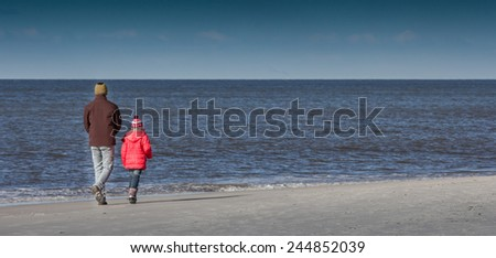 A proud dad and his cute daughter walking along a North Sea beaxh in winter