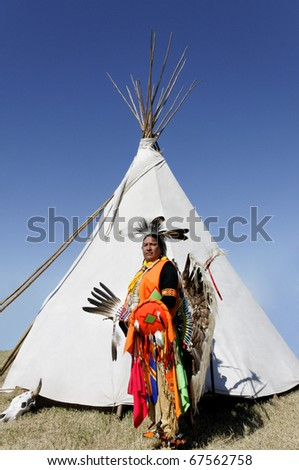 A proud Northern Cherokee indian man wearing full ceremonial dress and standing in front of a tee pee. - stock photo