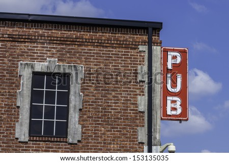 A Pub Sign Located On The Side Of Brick Building