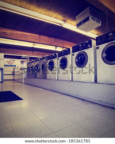 a public coin operated laundry mat done with a retro vintage instagram filter  - stock photo