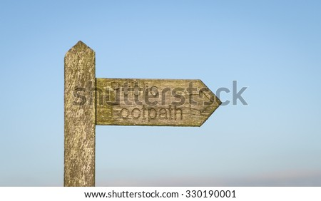 A Public footpath sign set against a light blue sky - stock photo