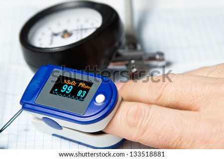 A pulse oximeter used to measure pulse rate and oxygen levels with Sphygmomanometer and ECG background - stock photo