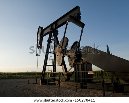 A pumpjack on the middle of the corn field near the Denver International Airport. - stock photo