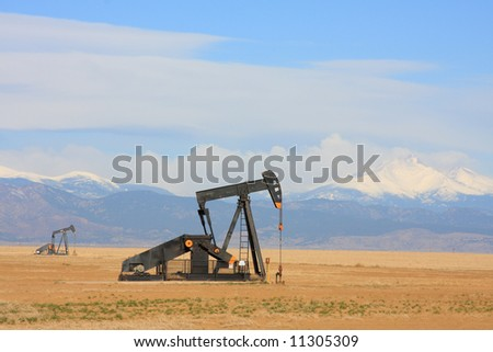 A Pumpjack pumping oil from an oil well in the plains with snow capped mountains in the backgroud. - stock photo