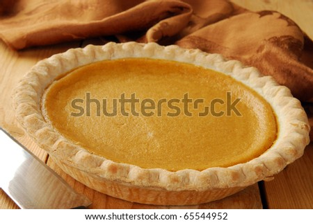 A pumpkin pie on a cutting board with a knife - stock photo