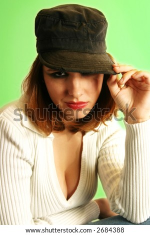 A punkish girl adjusts her army-style cap. - stock photo