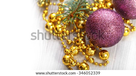 A purple globes on a gold bead and a sprig of fir
