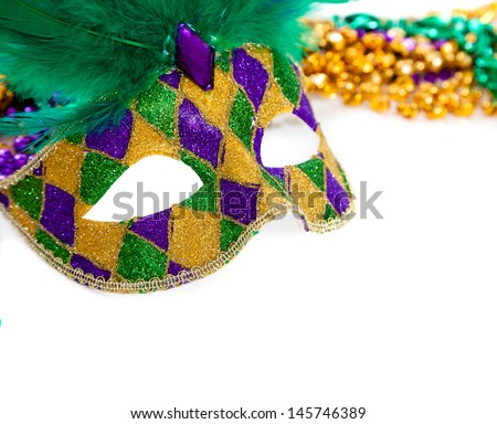 A purple, gold and green mardi gras mask and beads on white - stock photo