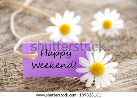 A Purple Label with Happy Weekend on it and white Flowers in the Background - stock photo