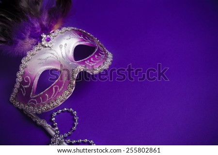 A purple mardi gras mask on a purple background with beads.  Carnivale costume. - stock photo