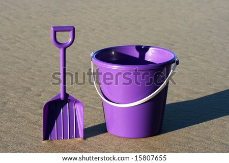 A purple plastic bucket and spade on the beach - stock photo