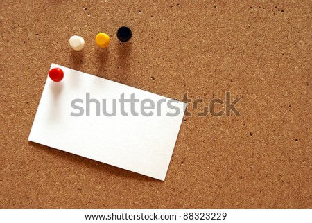 A pushpin is holding a blank notecard on a cork board. - stock photo