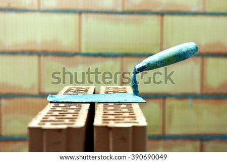 A putty knife or mason's trowel resting on a stack of bricks after a construction of a wall in the background. Inside of a building site at the end of a masonry work. - stock photo