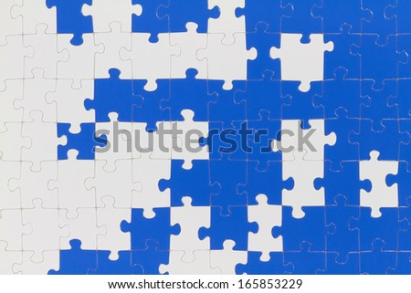 A puzzle is made up of puzzle pieces in two colors.