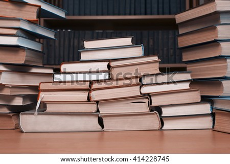 A pyramid of  books on the table-background of bookshelves - stock photo