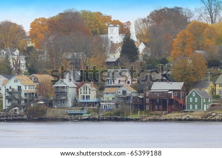 a quaint new england town's houses  on the water where the boats carry passengers - stock photo