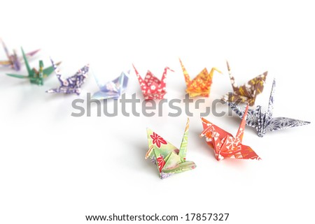 A queue of colorful origami birds on a white background - stock photo
