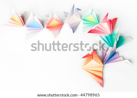A queue of colorful origami birds on a white background. High key soft focus. - stock photo