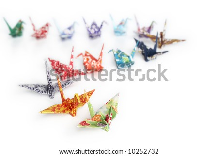 A queue of origami birds on a white background - stock photo